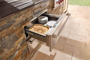 "Wolf 30"" Outdoor Warming Drawer (WWD30O) shown in a gourmet outdoor cooking area featuring best in quality Wolf cooking appliances"