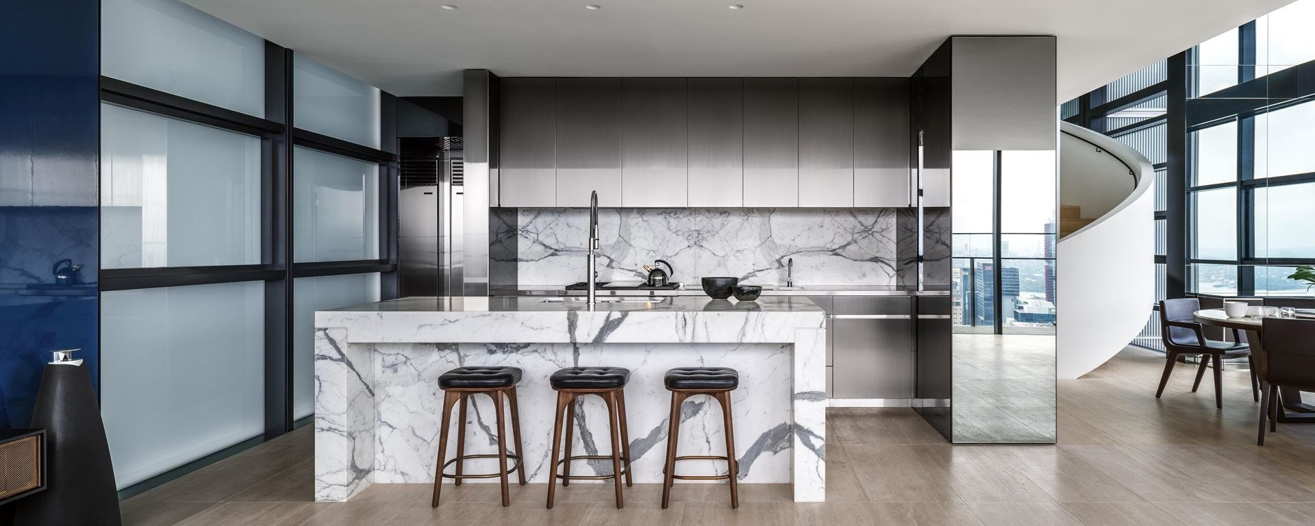 The Lumiere Penthouse kitchen design featuring Sub-Zero Refrigeration blending seamlessly into smooth minimalist cabinetry