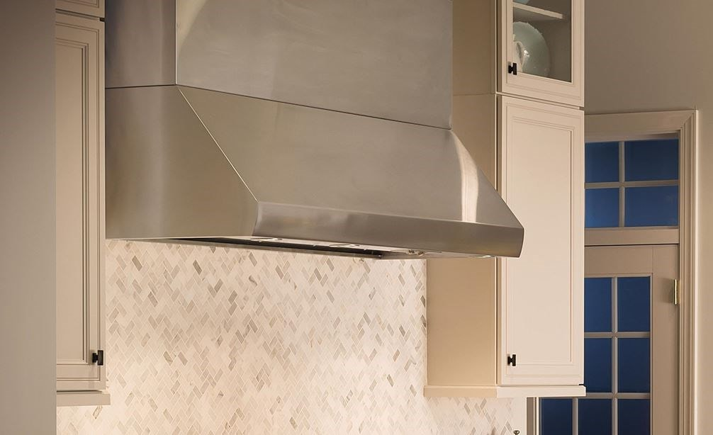 "Wolf 60"" Pro Wall Hood 24"" Depth (PW602418) is a timeless beauty in this elegant French inspired kitchen using white cabinets and marble countertop"