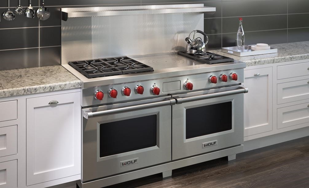 "The Wolf 60"" Dual Fuel Range 6 Burner French Top (DF606F) shown with light marble countertops along with classic white kitchen cabinetry"