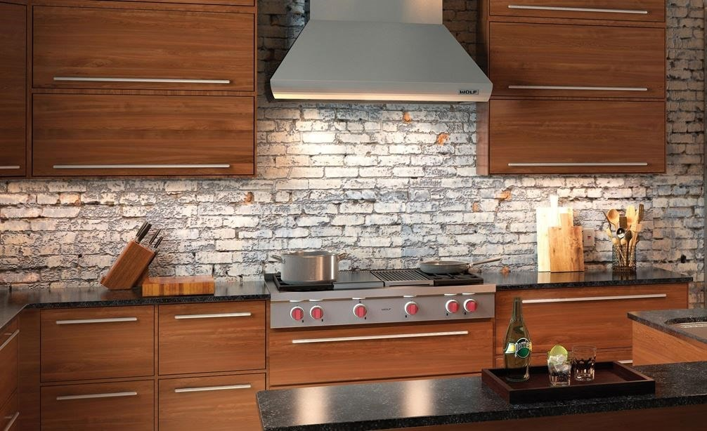 "The Wolf 48"" Sealed 4 Burner Rangetop Infrared Charbroiler and Griddle (SRT484CG) is timeless in this open kitchen featuring exposed brick"