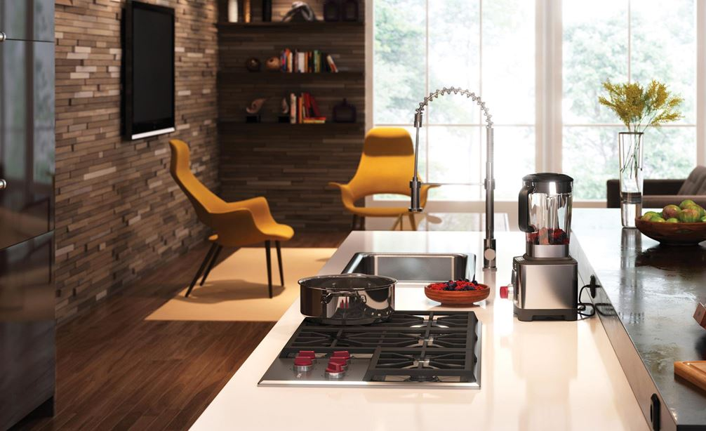 "The Wolf 36"" Professional Gas Cooktop (CG365P/S) displayed in large center island surrounded by an array of rich earthy tones and textures"