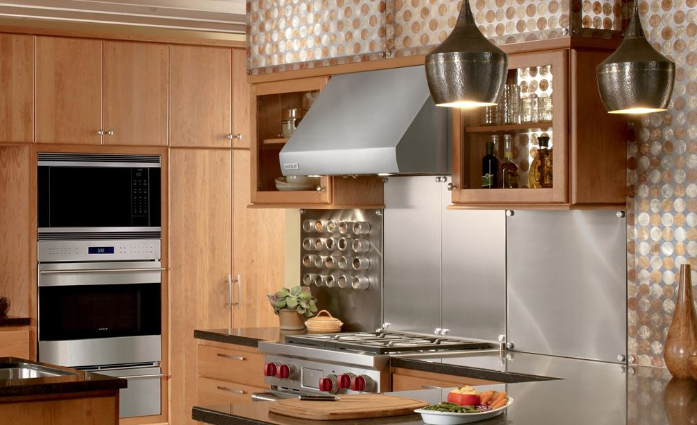 "Wolf 30"" Pro Wall Hood - 24"" Depth (PW302418) shown in modern open kitchen concept with stainless steel backsplash and exposed ceiling beams"