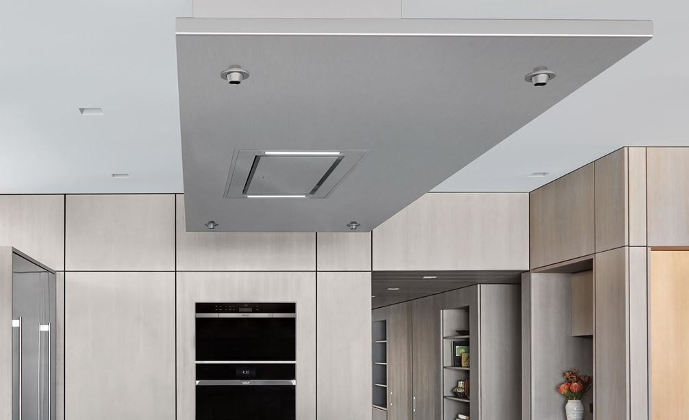 "Wolf 36"" Ceiling Mounted Hood Stainless Steel (VC36S) shown blending seamlessly above large kitchen island in modern minimalist kitchen"
