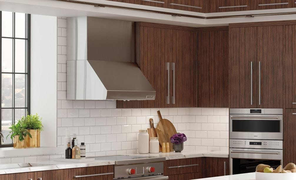"Wolf 36"" Pro Wall Hood - 24"" Depth (PW362418) shown in large open kitchen featuring warm wood tones with stainless steel accents"
