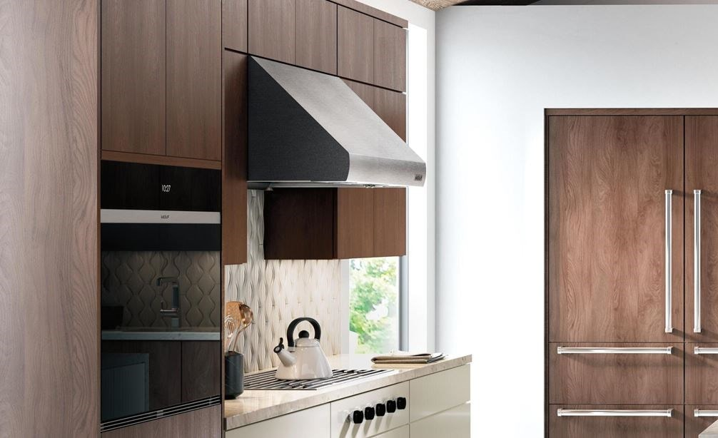"The Wolf 36"" Pro Wall Hood - 27"" Depth (PW362718) shown in a large luxury kitchen concept featuring smooth wood panel cabinetry"