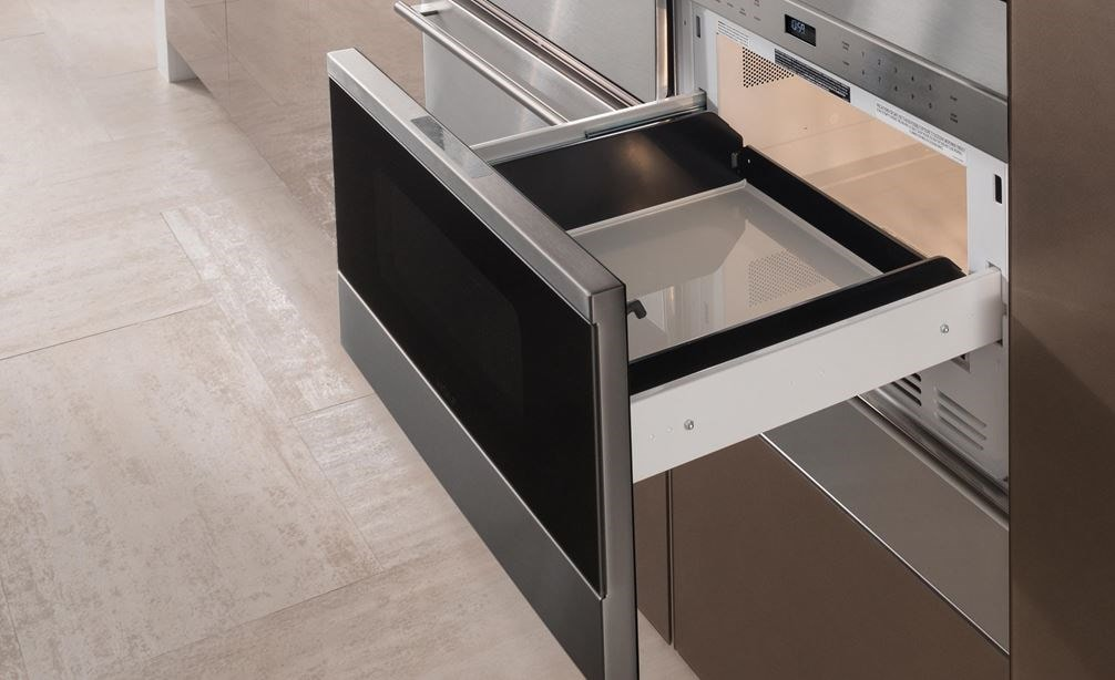 "The Wolf 24"" Transitional Drawer Microwave (MD24TE/S) shown here adding polish set flush in a wall of ultra-modern smooth cabinetry"