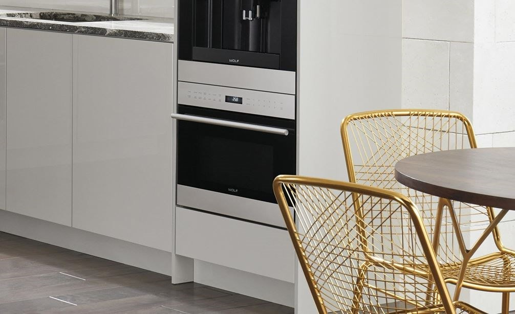 "Wolf 24"" E series Transitional Drop-Down Door Microwave Oven (MDD24TE/S/TH) shown in an open, fresh, light and functional modern kitchen"