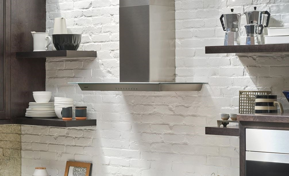 "The Wolf 36"" Cooktop Wall Hood - Glass (VW36G) shown set against white exposed brick and floating shelves in a luxury kitchen design"