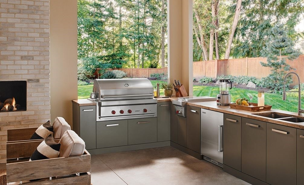 "The Wolf 42"" Outdoor Gas Grill (OG42) shown in a contemporary outdoor kitchen space offering comfort and professional kitchen amenities."