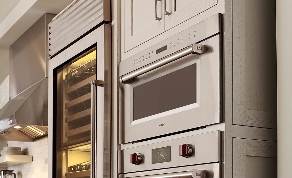 "Wolf 30"" M series Professional Drop-Down Door Microwave Oven (MDD30PM/S/PH) displayed in a classic medium tone wood floor kitchen design"