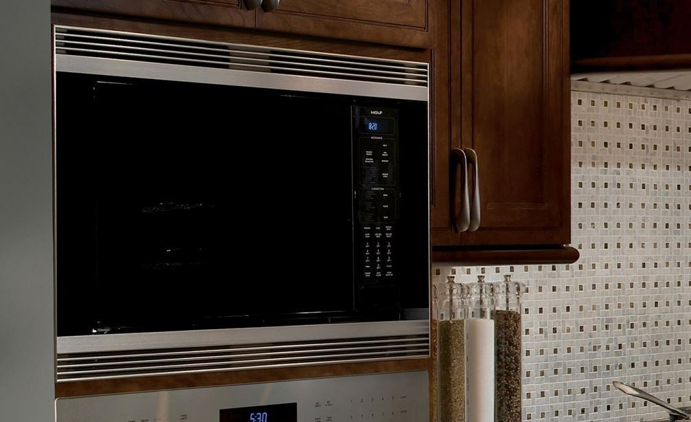 "The Wolf 24"" Convection Microwave Oven (MC24) sleek black design adds depth to this kitchen featuring stainless steel Wolf appliances"