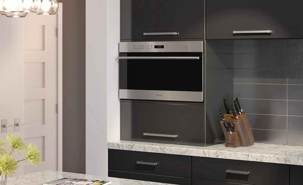 "Wolf 30"" E Series Transitional Drop-Down Door Microwave Oven (MDD30TE/S/TH) set expertly in smooth cabinetry against gray backsplash"