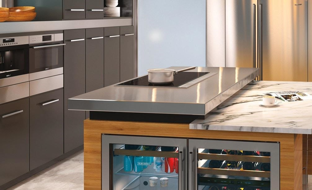 "The Wolf 36"" Transitional Induction Cooktop (CI365T/S) shown set in stainless steel countertop in an ultra modern sleek kitchen design"