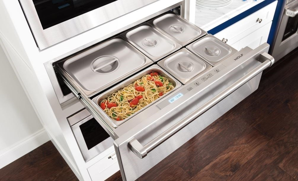 "The Wolf 30"" Warming Drawer (WD30) displaying it's capacity for holding several dishes while looking great with dark wood floors"