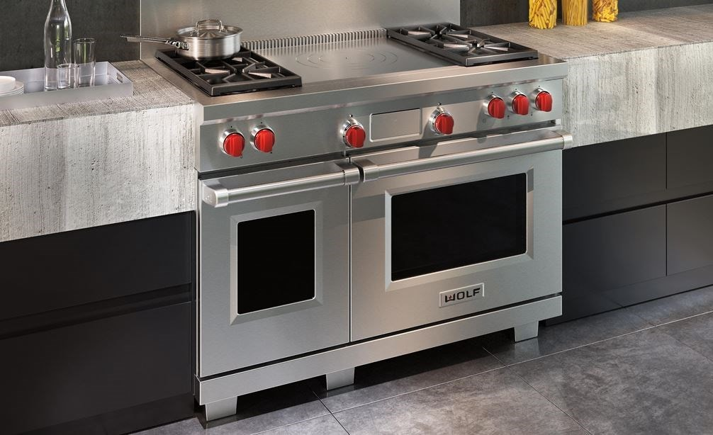 "Wolf 48"" Dual Fuel Range 4 Burner French Top (DF484F) shown with concrete and minimalist kitchen cabinets in an ultra-modern kitchen"