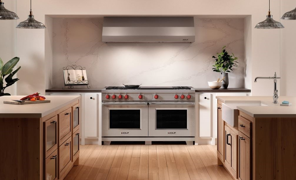Wolf 60-inch Dual Fuel Range with Frenchtop set between two kitchen islands below Wolf Pro Ventilation.
