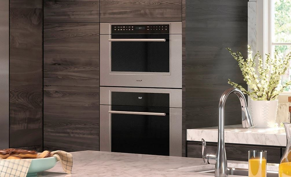 "Wolf 30"" M Series Transitional Drop-Down Door Microwave Oven (MDD30TM/S/TH) framed in large wood panel cabinetry in contemporary kitchen"