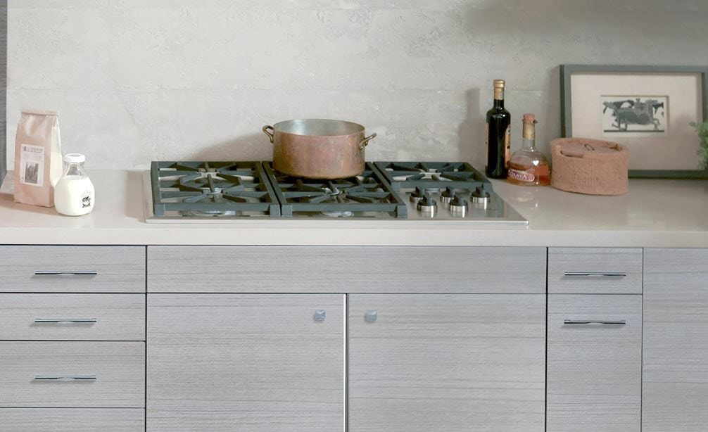 "The Wolf 36"" Professional Gas Cooktop (CG365P/S) featured in a bright open kitchen awash in subtle textures and artful display shelves"