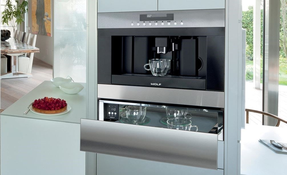 "The Wolf 24"" Cup Warming Drawer Stainless Steel (CW24/S) shown integrated into a modern clean-lined l-shaped kitchen"
