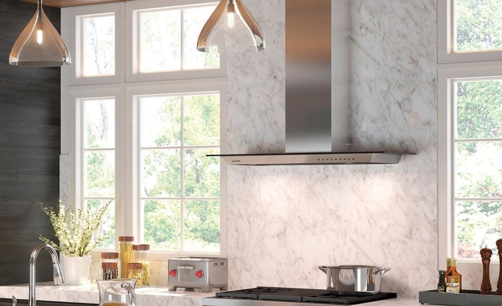 "The Wolf 36"" Cooktop Wall Hood - Glass (VW36G) shown centered on large textured backsplash between large windows in open kitchen design"