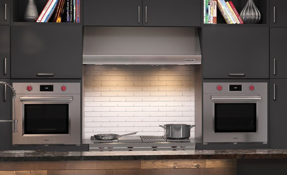 "Wolf 30"" M Series Professional Single Ovens (SO30PM/S/PH) shown on each side of a Wolf 48"" Pro Wall Hood - 24"" Depth (PW482418)"