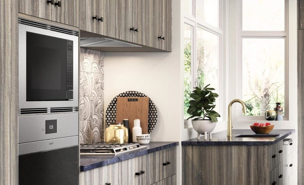 "Wolf 24"" Standard Microwave Oven (MS24) shown in open rustic kitchen design featuring warm toned concrete floors and wood panel cabinetry"