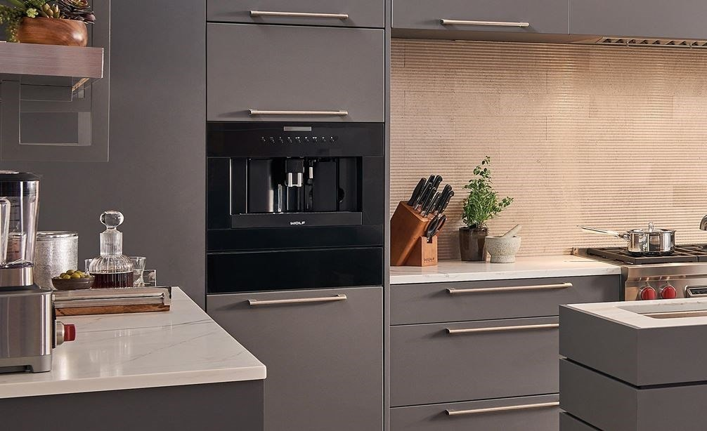 "The Wolf 24"" Cup Warming Drawer Black Glass (CW24/B) shown set flush in sleek gray cabinetry in a large and open metro kitchen design"