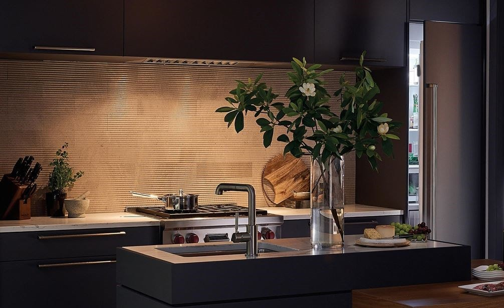 "The Wolf 34"" Pro Hood Liner - 19"" Depth (PL341912) shown illuminating cooking surface in large open kitchen featuring dark cabinetry"