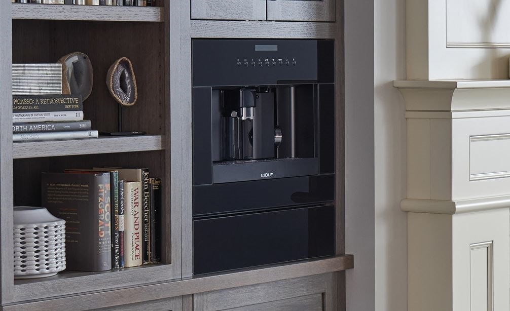 "The Wolf 24"" Coffee System Black Glass (EC24/B) shown set seamlessly in bookshelf featuring warm wood tones and modern handles"