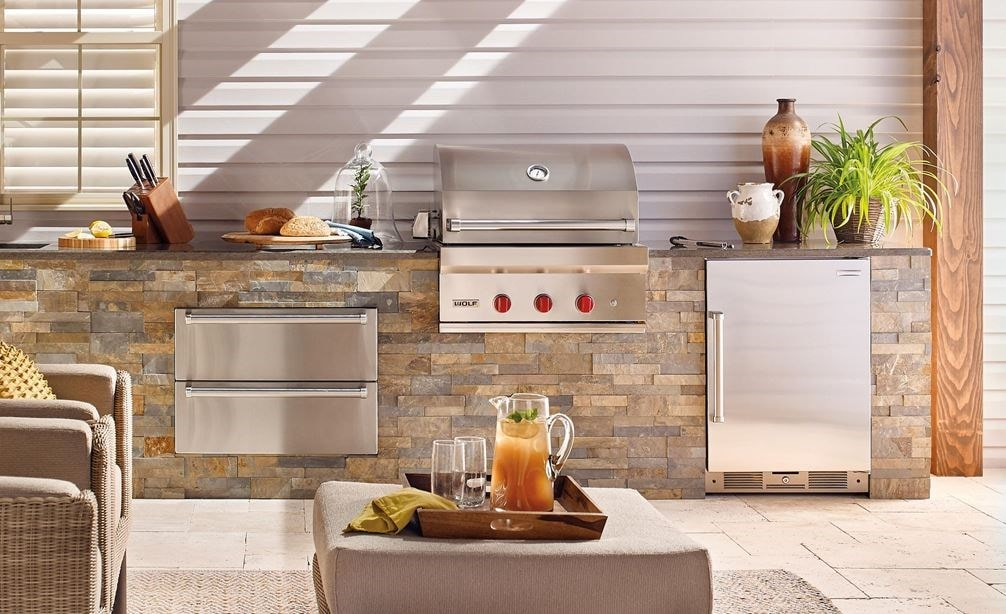 "The Wolf 30"" Outdoor Gas Grill (OG30) shown with Wolf 30"" Outdoor Warming Drawer (WWD30O) in a luxury outdoor kitchen space."