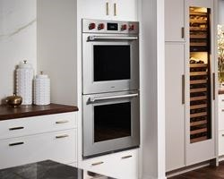 Wolf Built-In Double Wall Ovens displayed in white kitchen cabinets for a clean and stylish luxury kitchen space