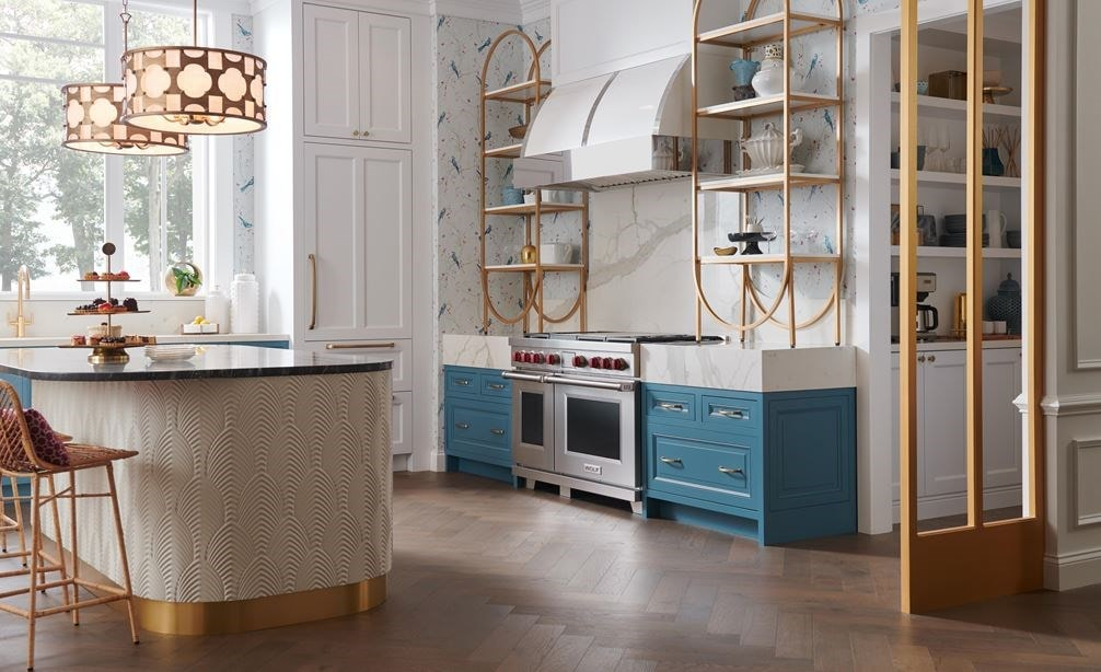 Wolf Dual Fuel Range set in a whimsical kitchen design featuring gold fixtures and pendant lights.