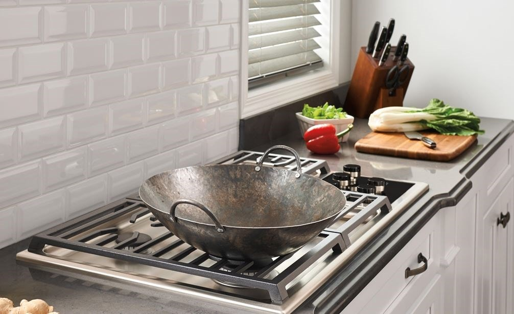 "The Wolf 36"" Transitional Gas Cooktop 5 Burners (CG365T/S) shown set in rich granite countertop against textured white brick backsplash"