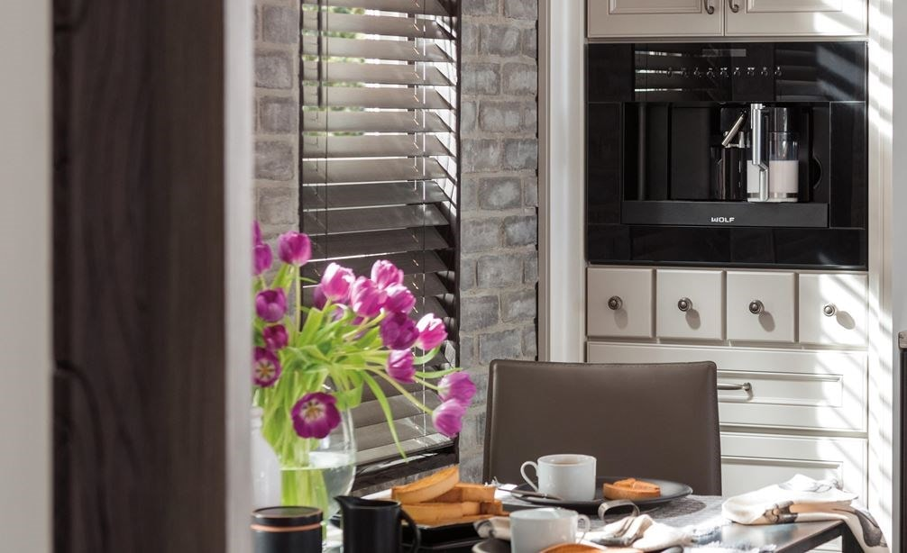 "Wolf 24"" Coffee System Black Glass (EC24/B) shown set flush in classic white country cabinet with artistic display shelves on wall"