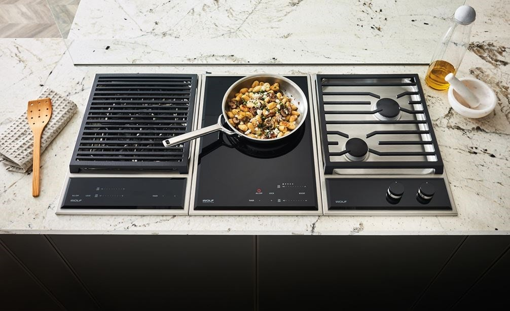 "The Wolf 15"" Transitional Induction Cooktop (CI152TF/S) shown set flush in artistic black and white speckled granite countertop"