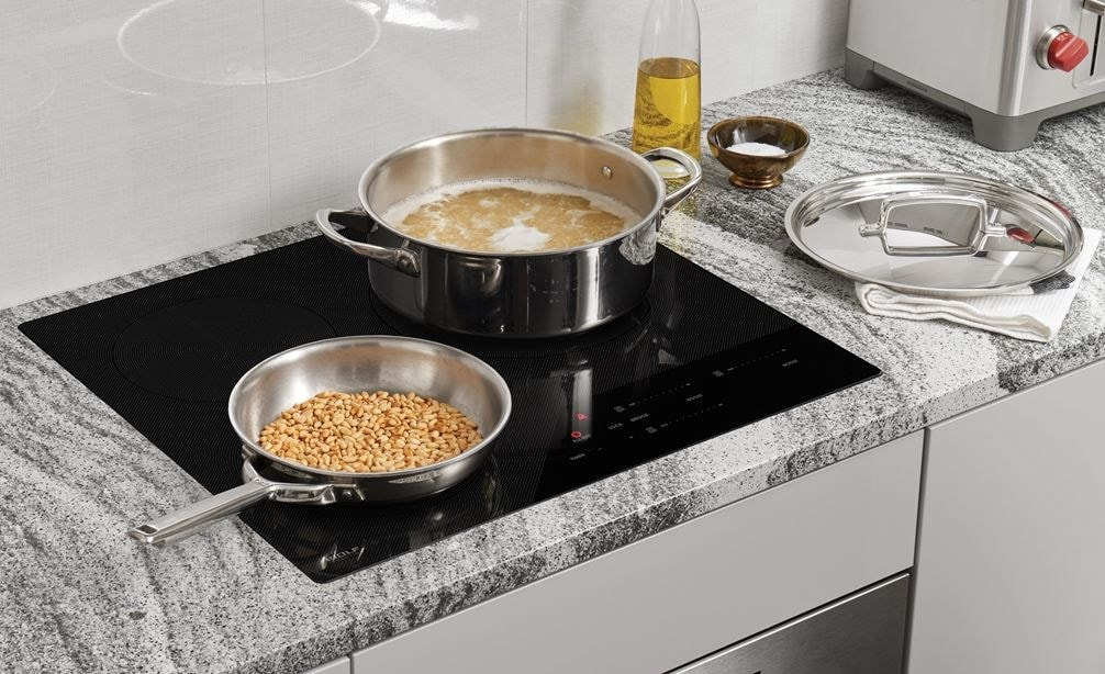 "Wolf 24"" Contemporary Induction Cooktop (CI243C/B) shown set flush in dark grey black and white swirl granite countertop"