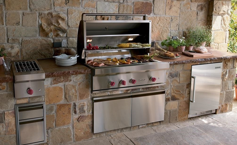 "The Wolf 42"" Outdoor Gas Grill (OG42) shown offering state-of-the-art kitchen amenities in a warm and rustic outdoor kitchen design."