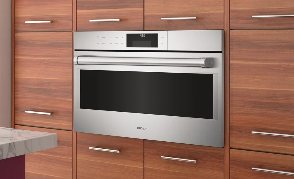 "The Wolf 30"" E Series Professional Convection Steam Oven (CSO30PE/S/PH) shown elevated and framed in a sophisticated cabinet style"